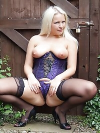 Amy poses outdoors in her stockings and basque